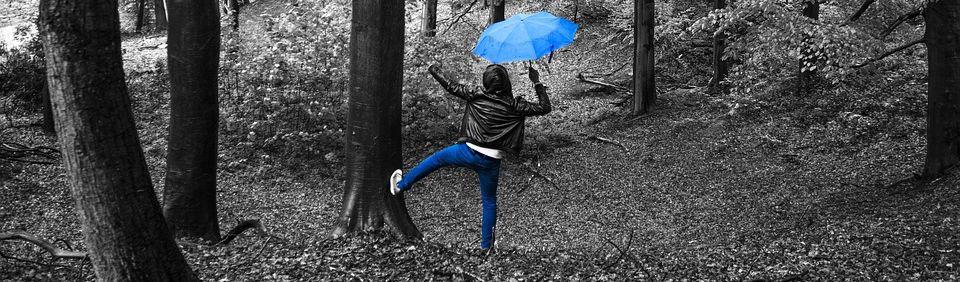 Frau im Wald mit blauem Schirm